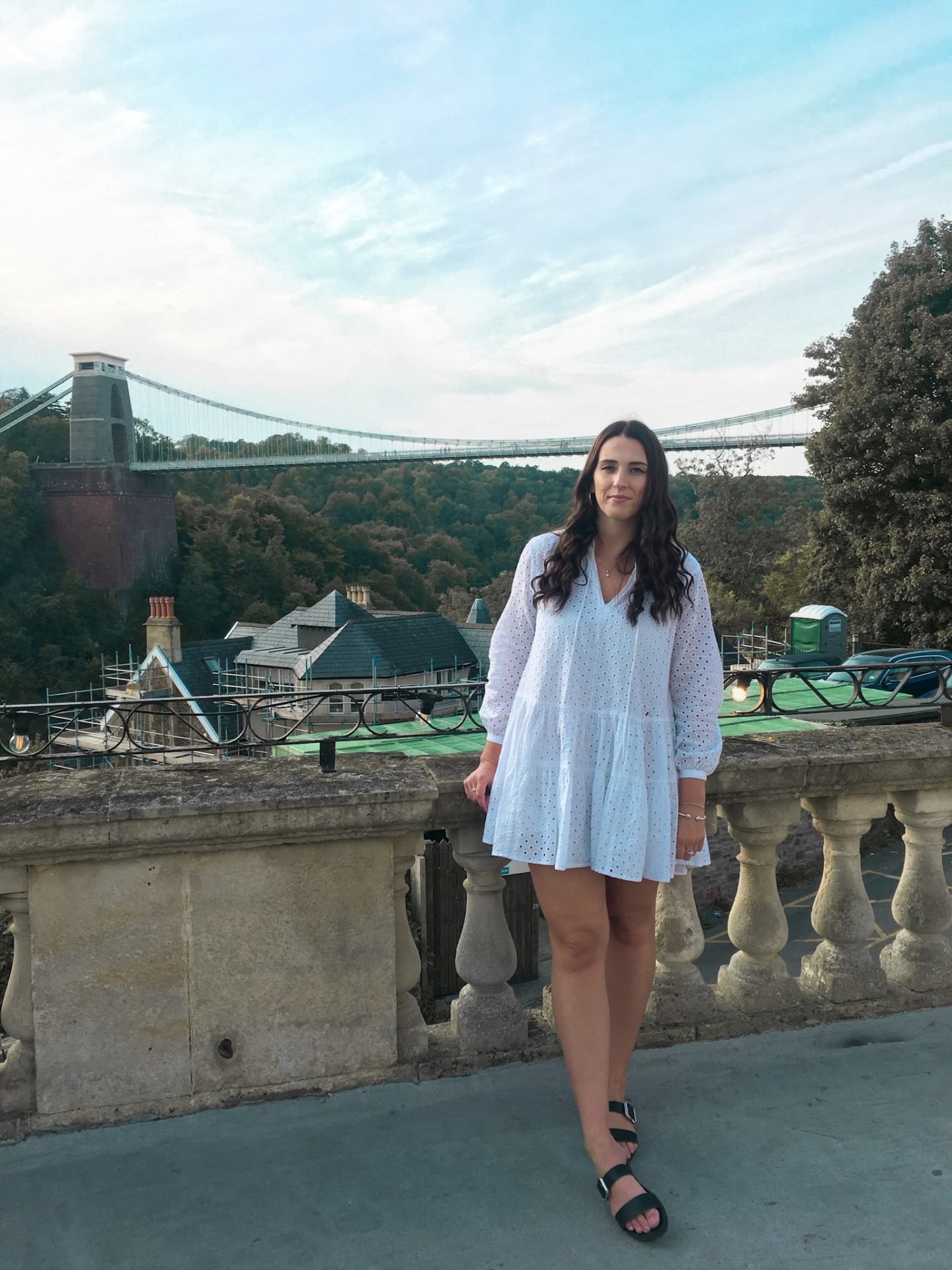 Girl in white dress looking at Bristol clifton suspension bridge