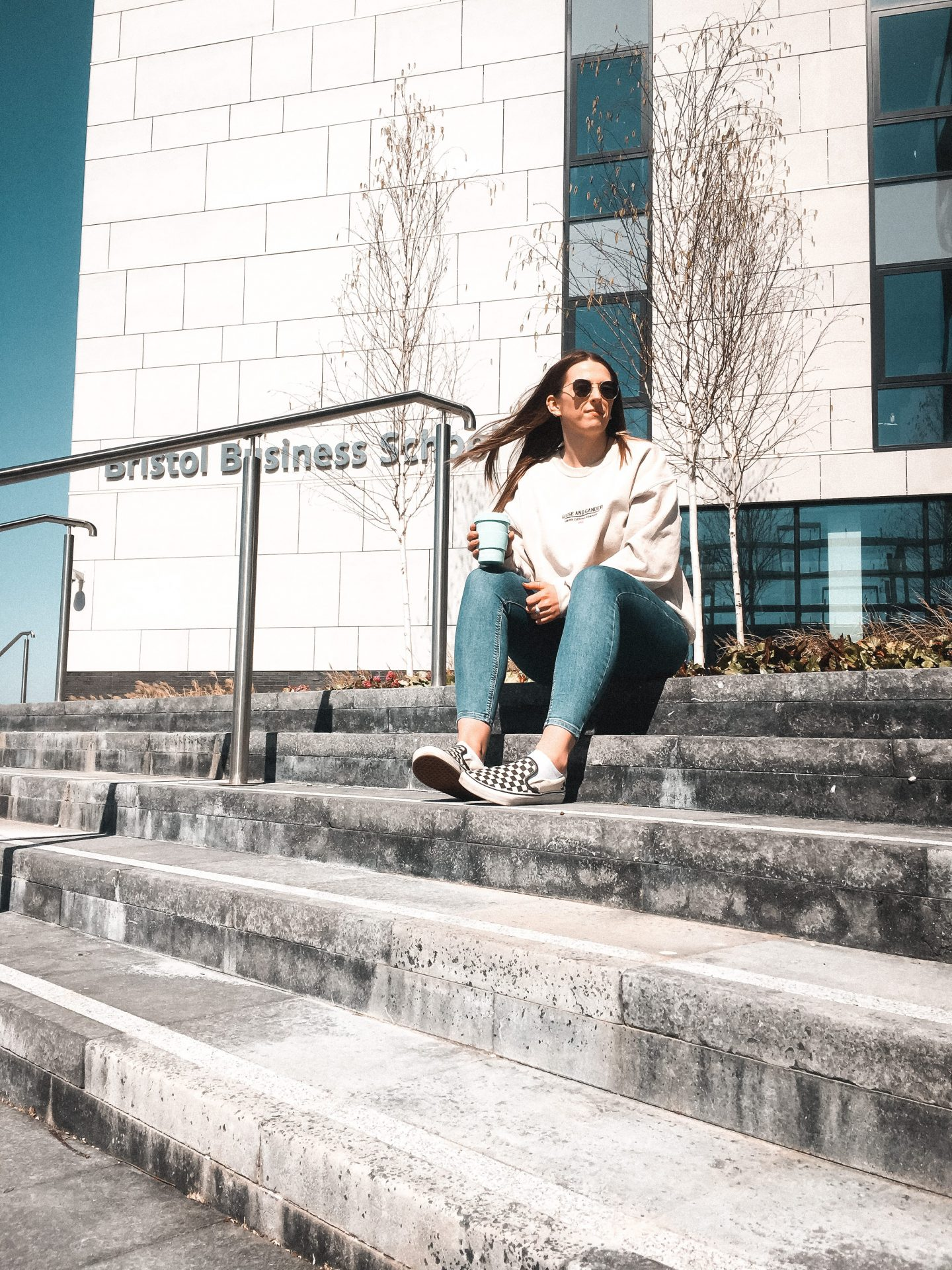 Girl sat on steps outside of UWE Bristol Business School