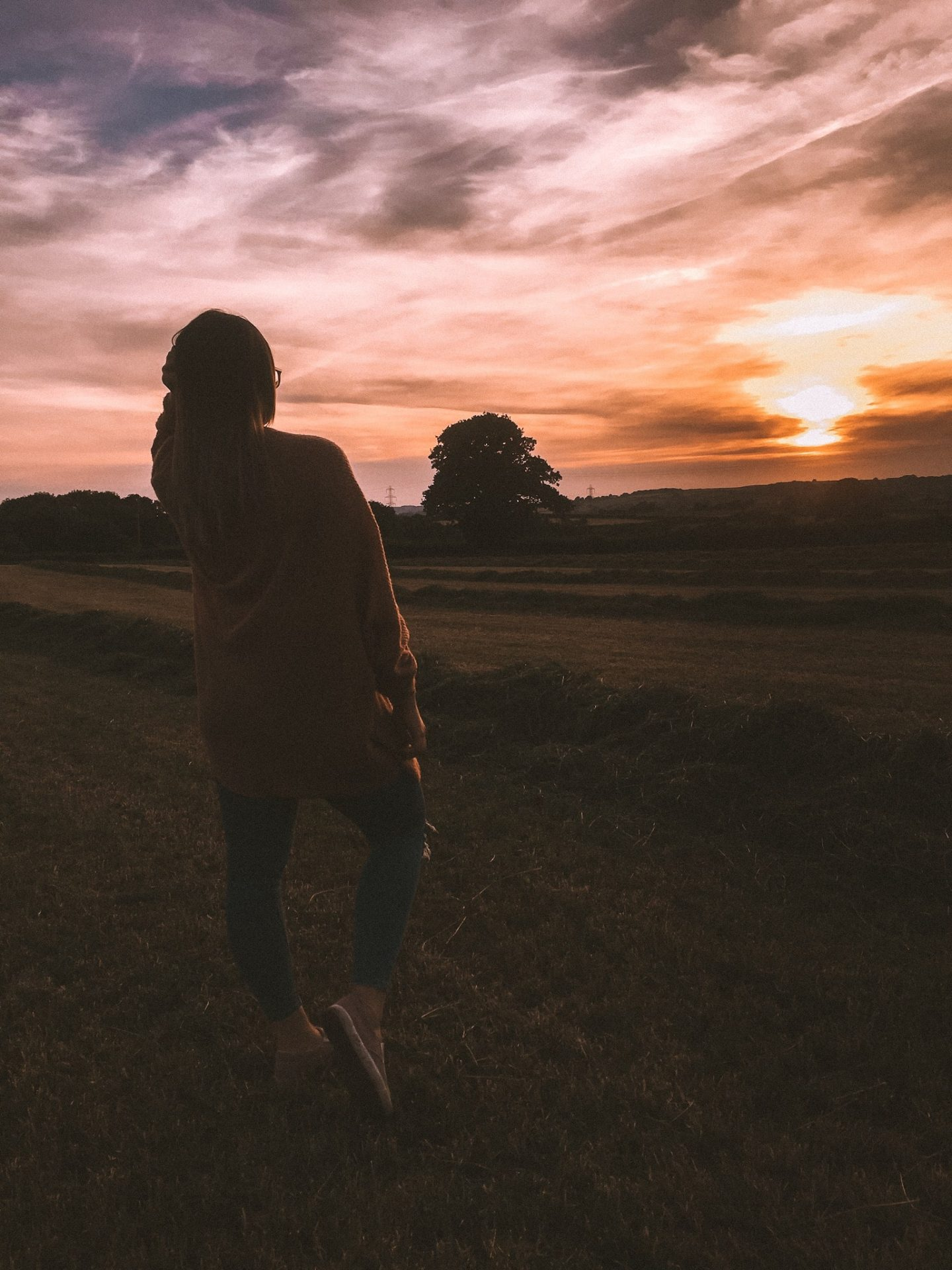 Girl stood at sunset in a field