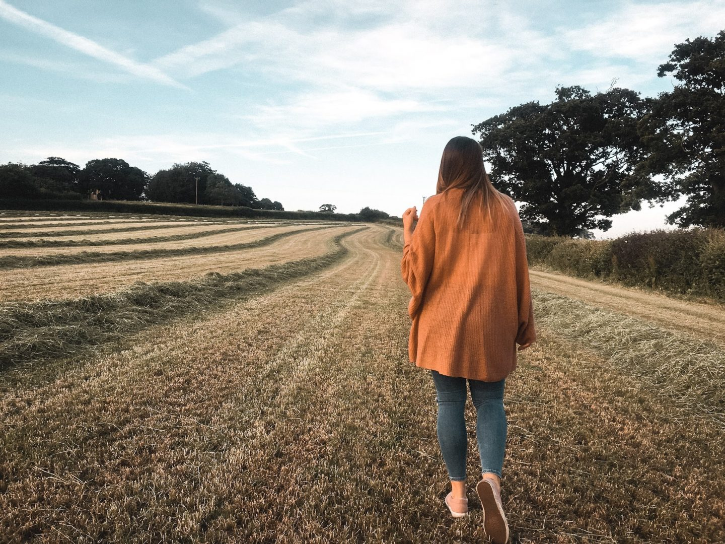 Girl walking in field during summer