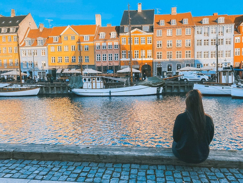 Girl sat alongside Nyhavn in Copenhagen, Denmark