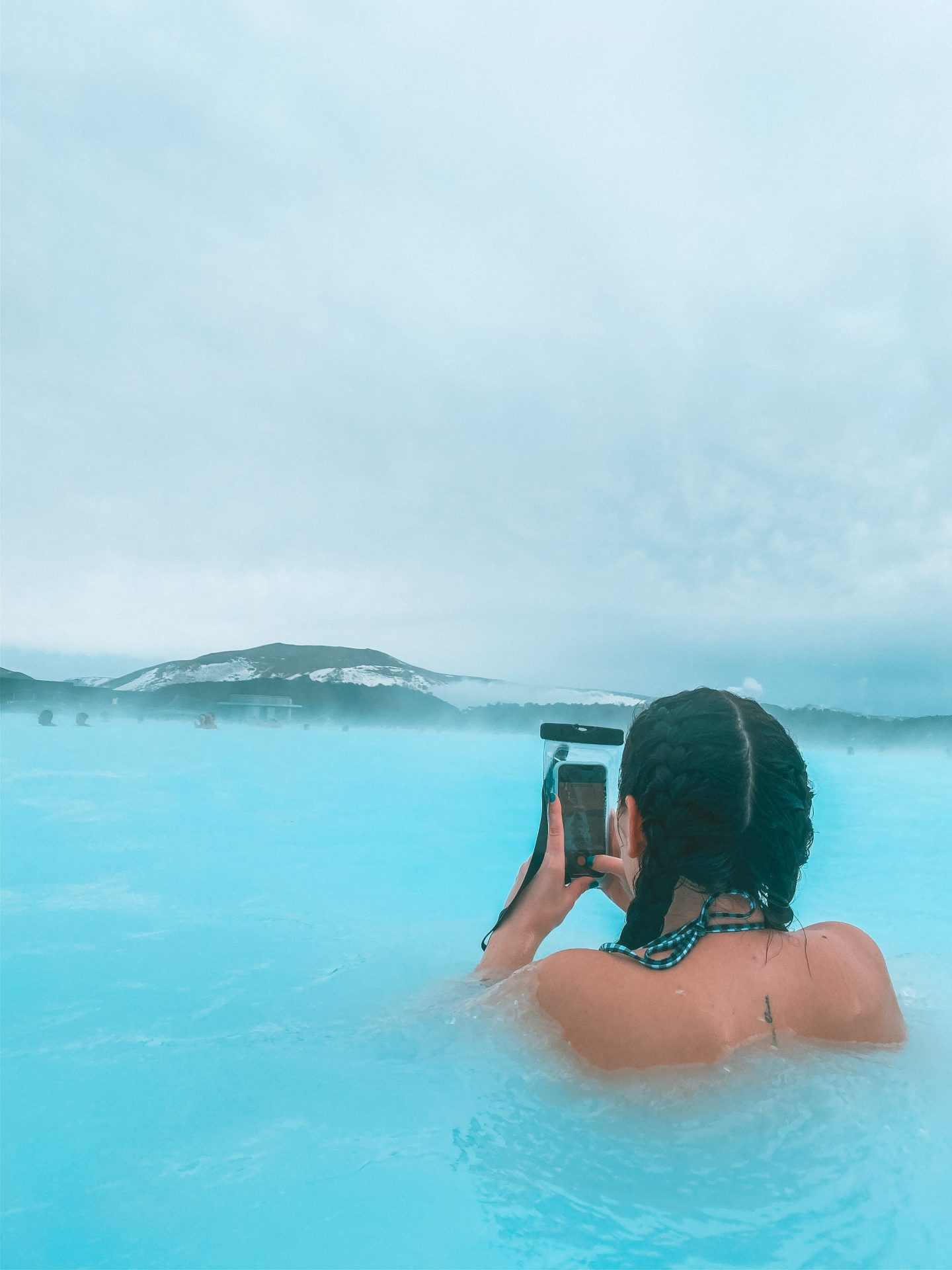 Girl taking picture in blue lagoon in iceland