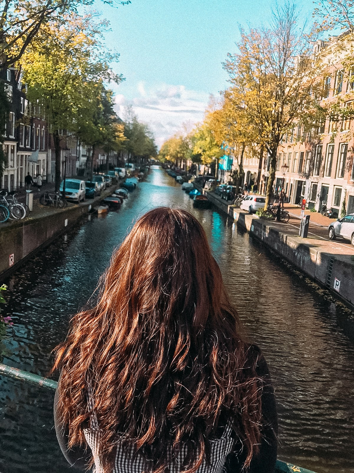 Curly haired girl looking over Amsterdam canal with blue skies